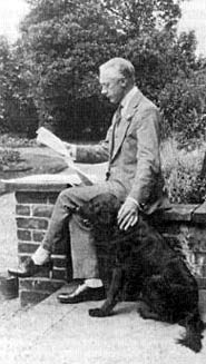 Picture of F. M. Alexander, reading a book with his dog beside him