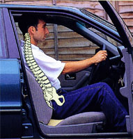 Man using wedge-shaped posture cushion in car benefits from improved posture