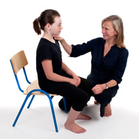 Alexander teacher helping young girl to sit with back more upright