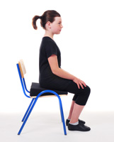 Young girl sitting in chair with improved posture after Alexander lesson