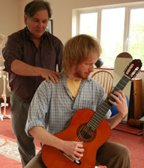 Student learning to play a guitar with less muscle tension and strain